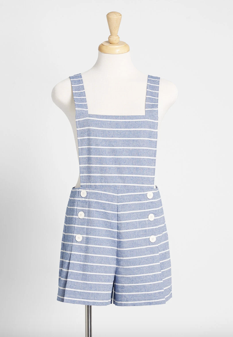 A light blue shortall with thin white horizontal stripes and pockets on the side with three buttons over each of them