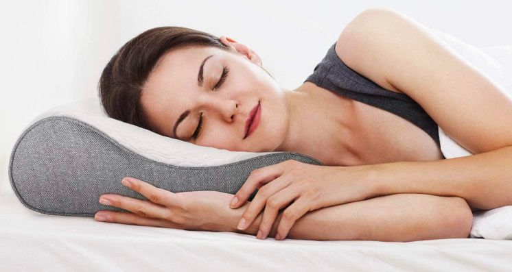 A model sleeping on their side. The contoured pillow is keeping their neck upright a healthy distance from their shoulder, preventing added pressure on the shoulder they are resting their weight on.