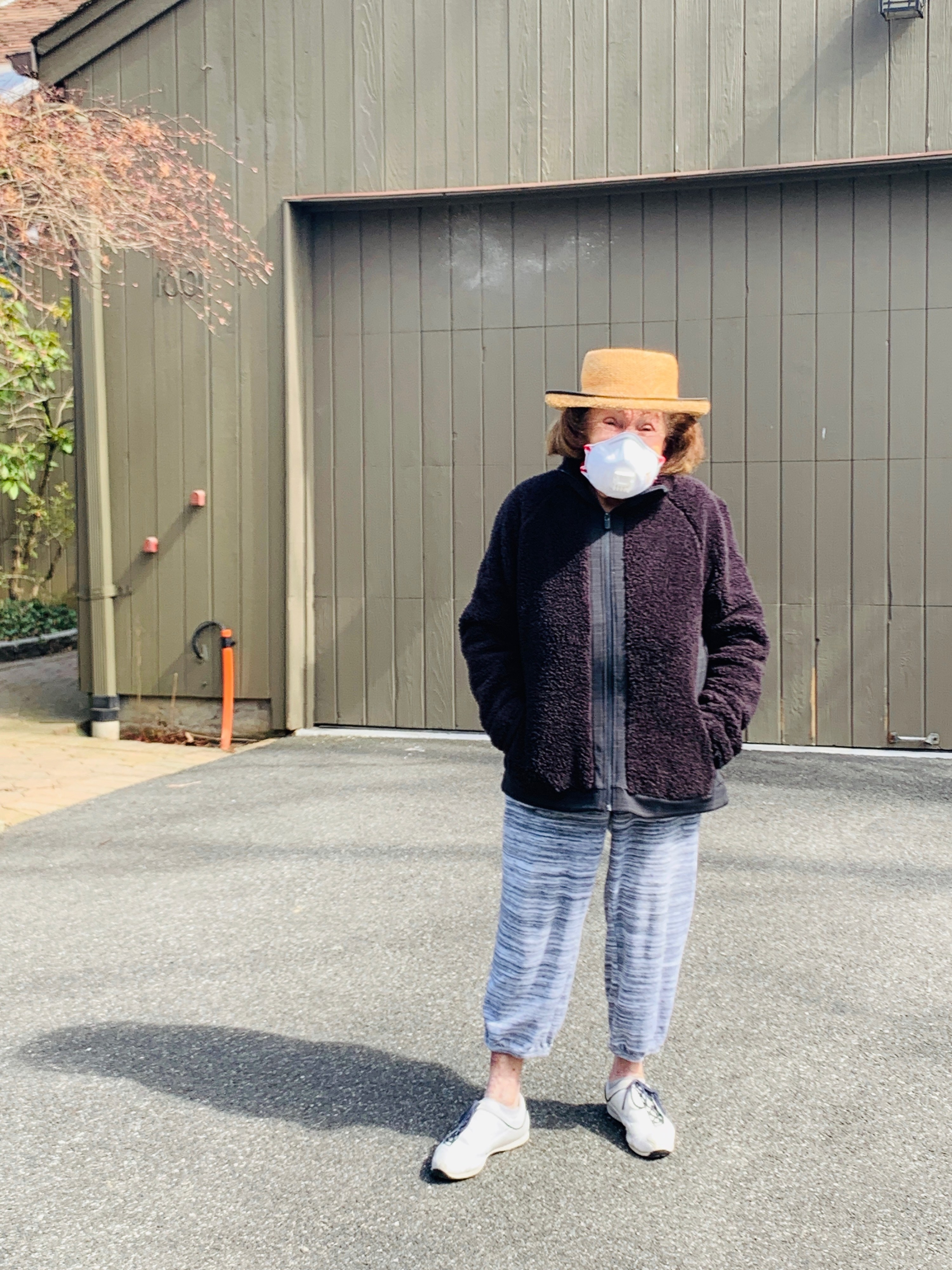 My grandmother standing outside her home in a beach hat and mask.