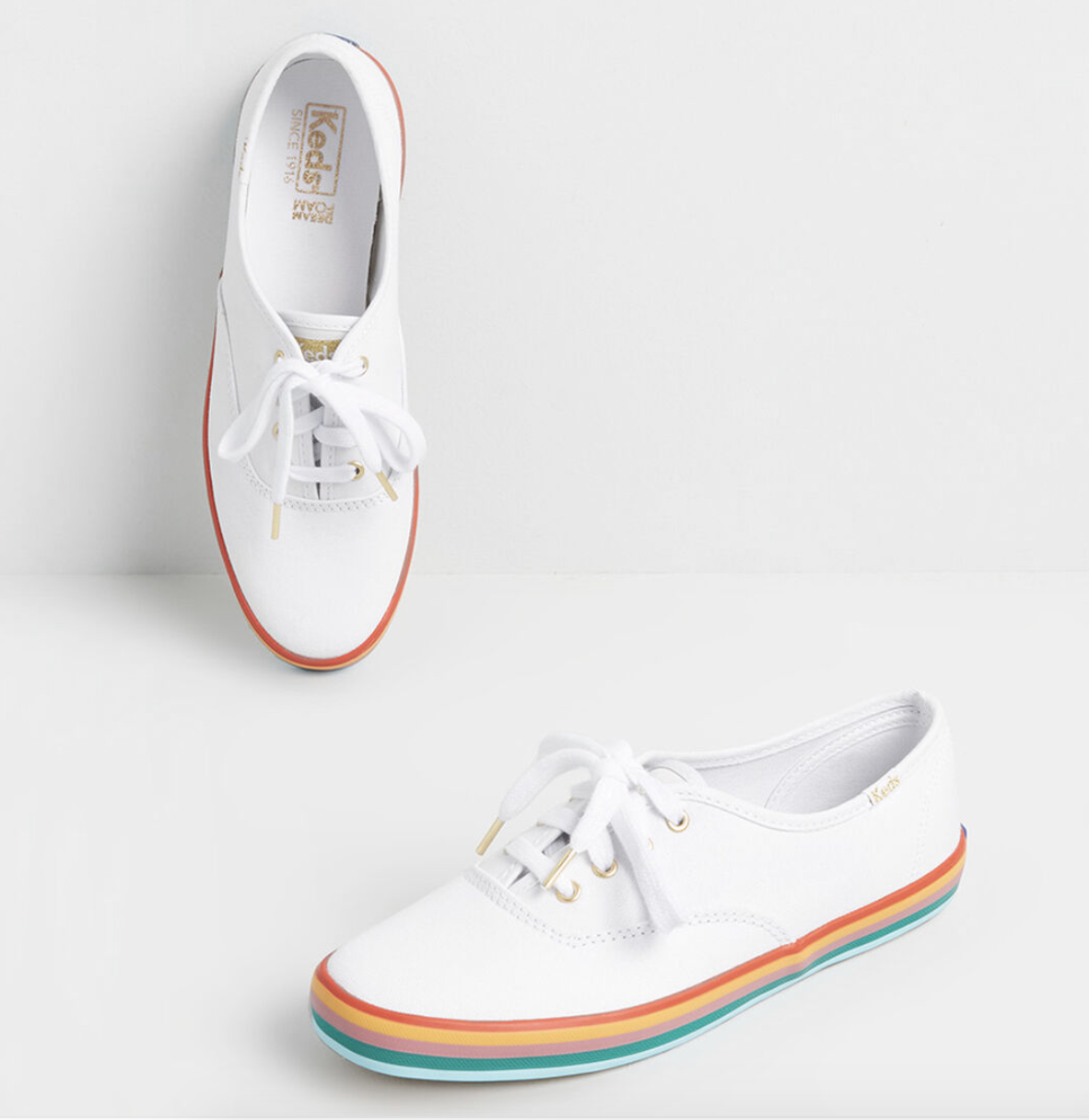 A pair of white Keds with pastel rainbow bottoms