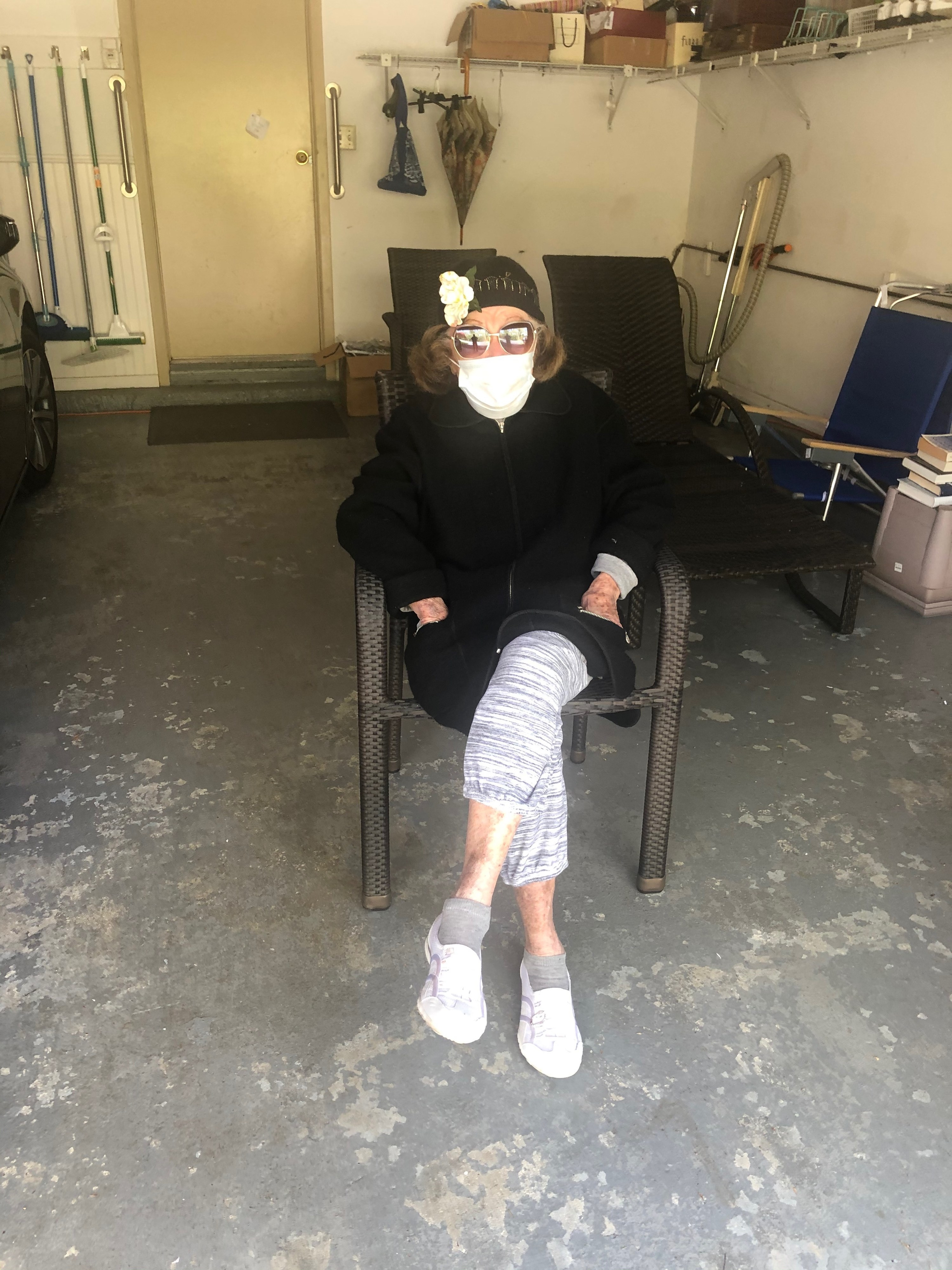 My grandmother sitting in her garage with visitors wearing a mask, a hat, and sunglasses.