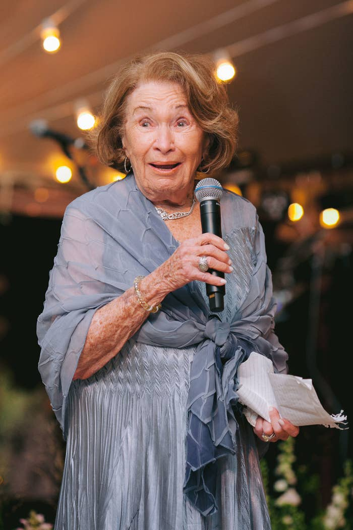 My grandmother with a microphone in hand, giving a speech at my wedding.