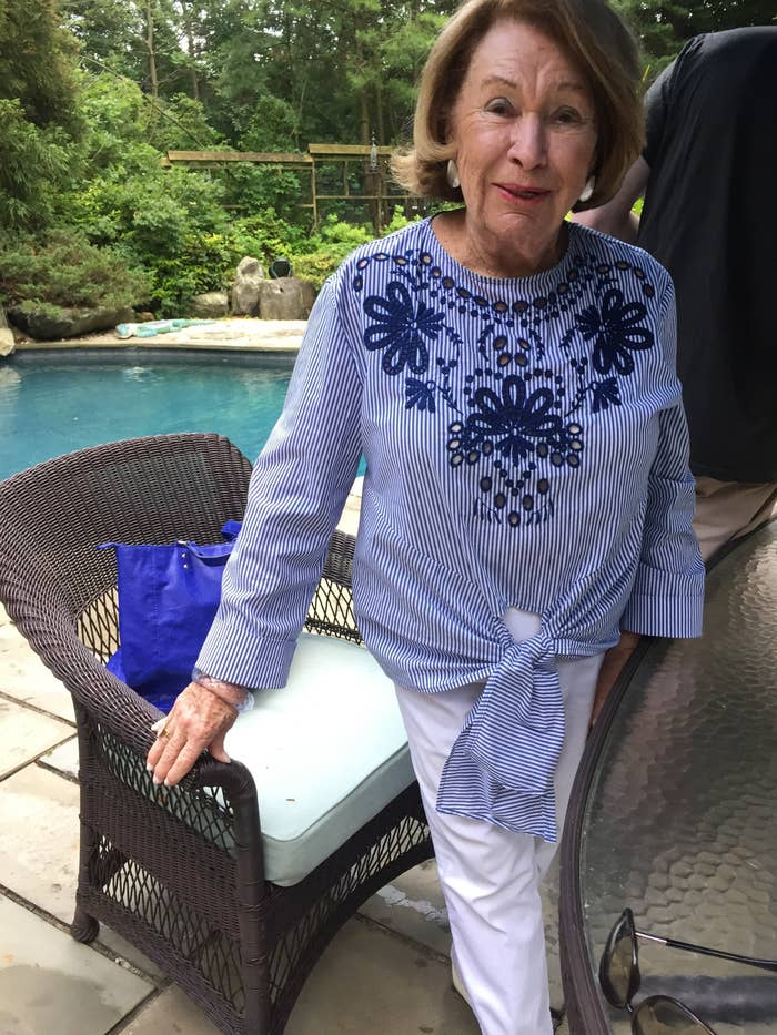 My grandma posing and looking stylish in white jeans and a blue blouse.