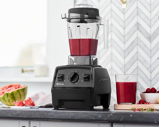 A black blender base with a clear plastic jar filled with a berry-based smoothie