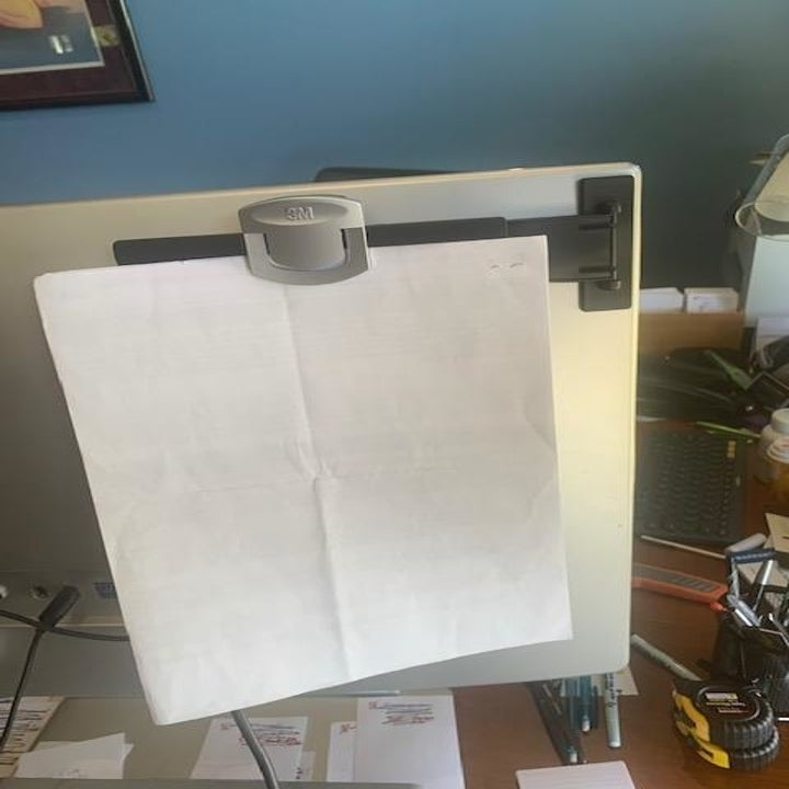 Same reviewer's photo showing the clip folds back behind the monitor so it's out of the way
