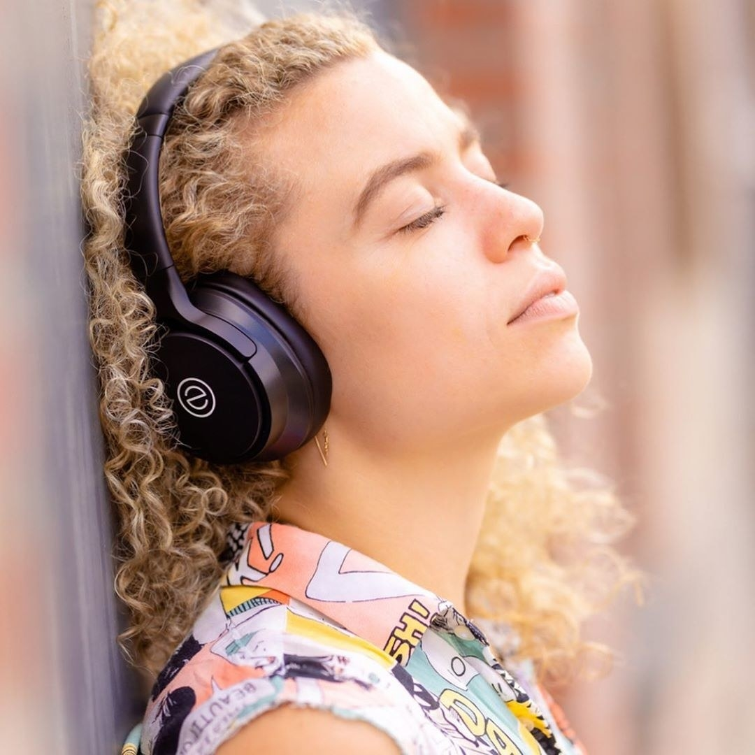 a woman with her eyes closed wearing over the ear headphones