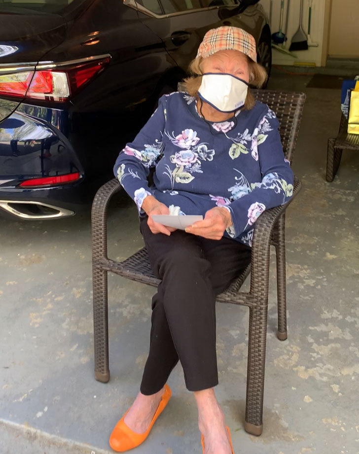 My grandma sitting in a chair in her garage wearing a mask.