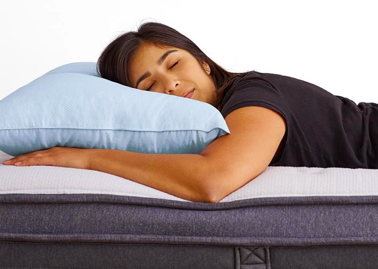 A model sleeping on their stomach with their face on the pillow and their arms outstretched underneath it