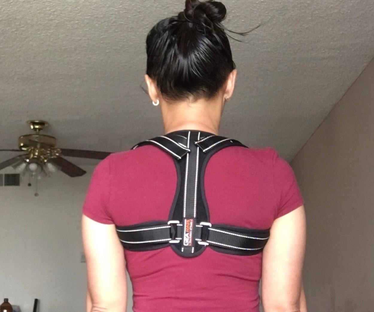 Reviewer wearing the brace over their shirt