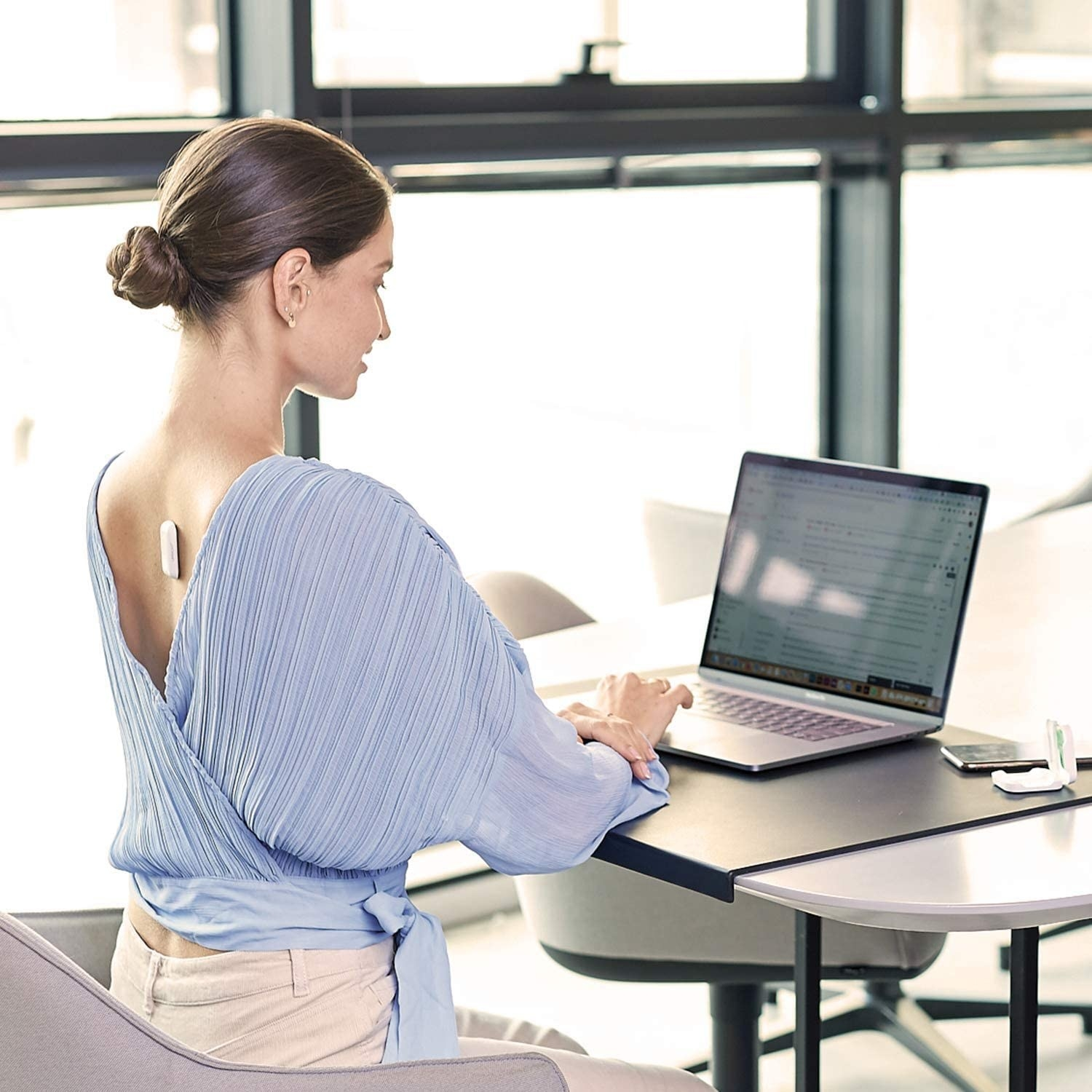 model wearing the white posture corrector directly on their back while sitting up straight and typing on a computer