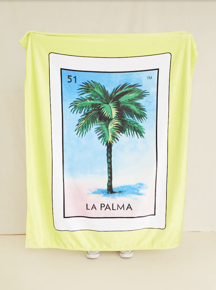 "a big yellow blanket with a middle design of a white Loteria card with a palm tree and the words ""la palma"" under it"