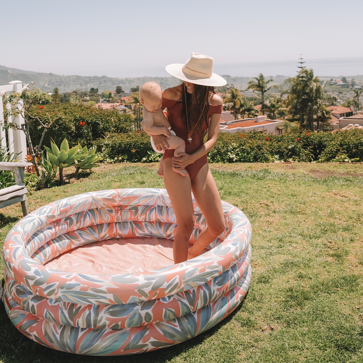a mom and her baby standing in the pool which has a floral pattern