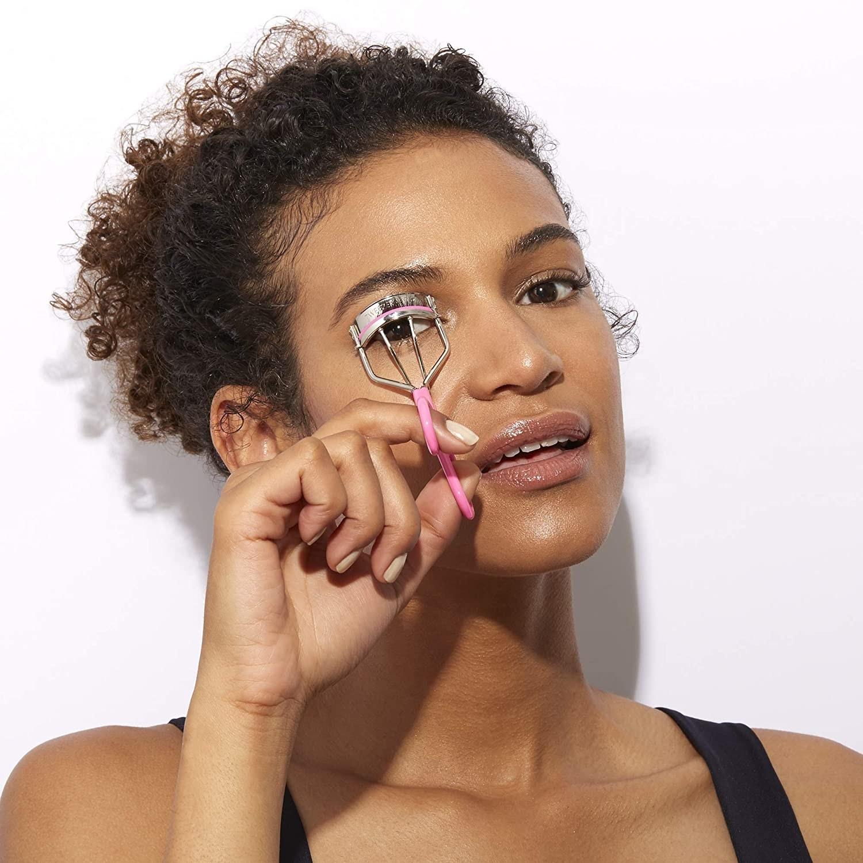 model using pink eyelash curler