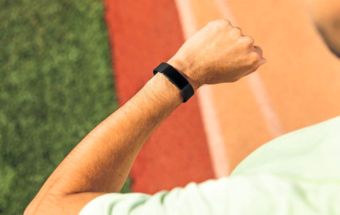 Model wears black Fitbit Inspire HR on their wrist while running on a track