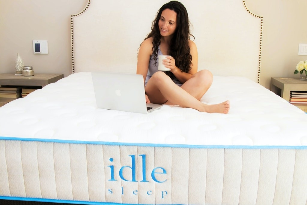 person sitting on a cushy looking mattress without bedding