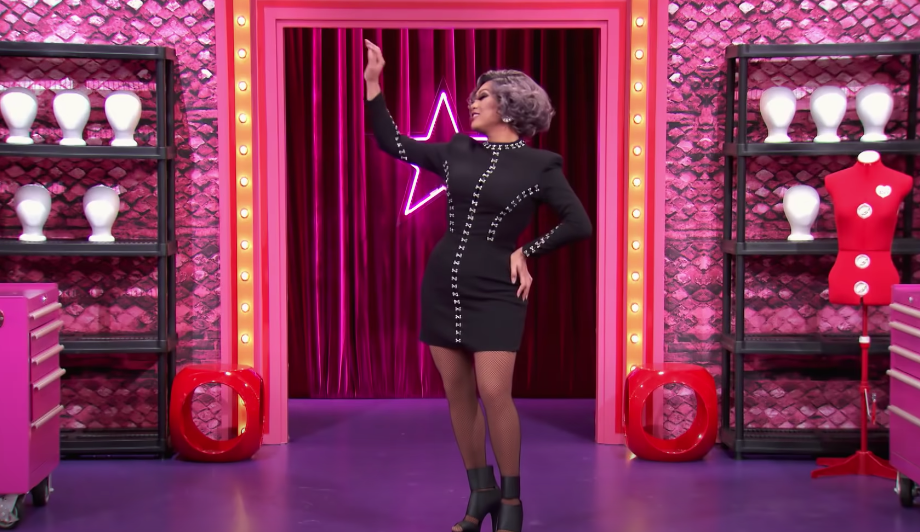 Juju walking into the Werk Room in a short long-sleeved black dress during All Stars 5