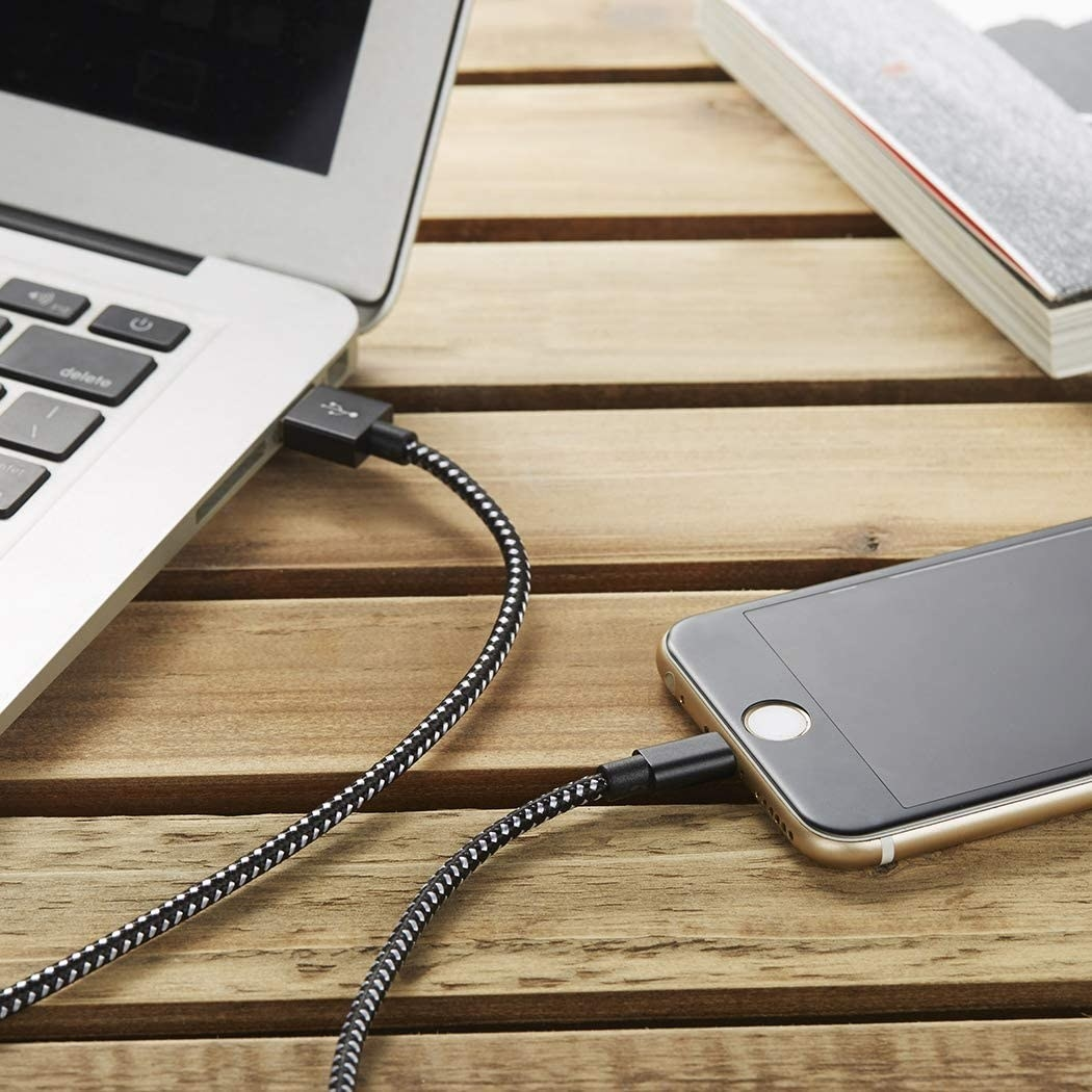 A charging cord plugged into a phone and into a laptop