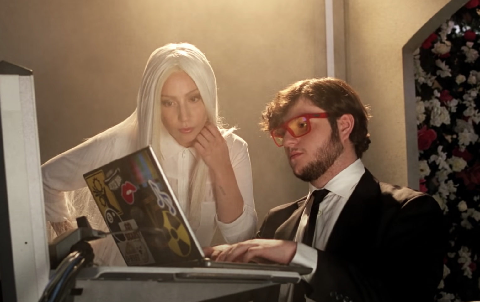 Lady Gaga looking at a computer that Adam Dahlberg is working on