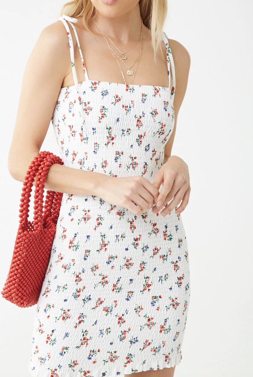 a model in a white stretchy smocked dress with tiny blue and red flowers all over it