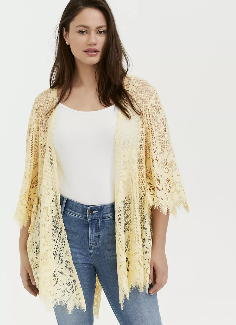 a model wearing the pale yellow floral laced poncho with scallop edges