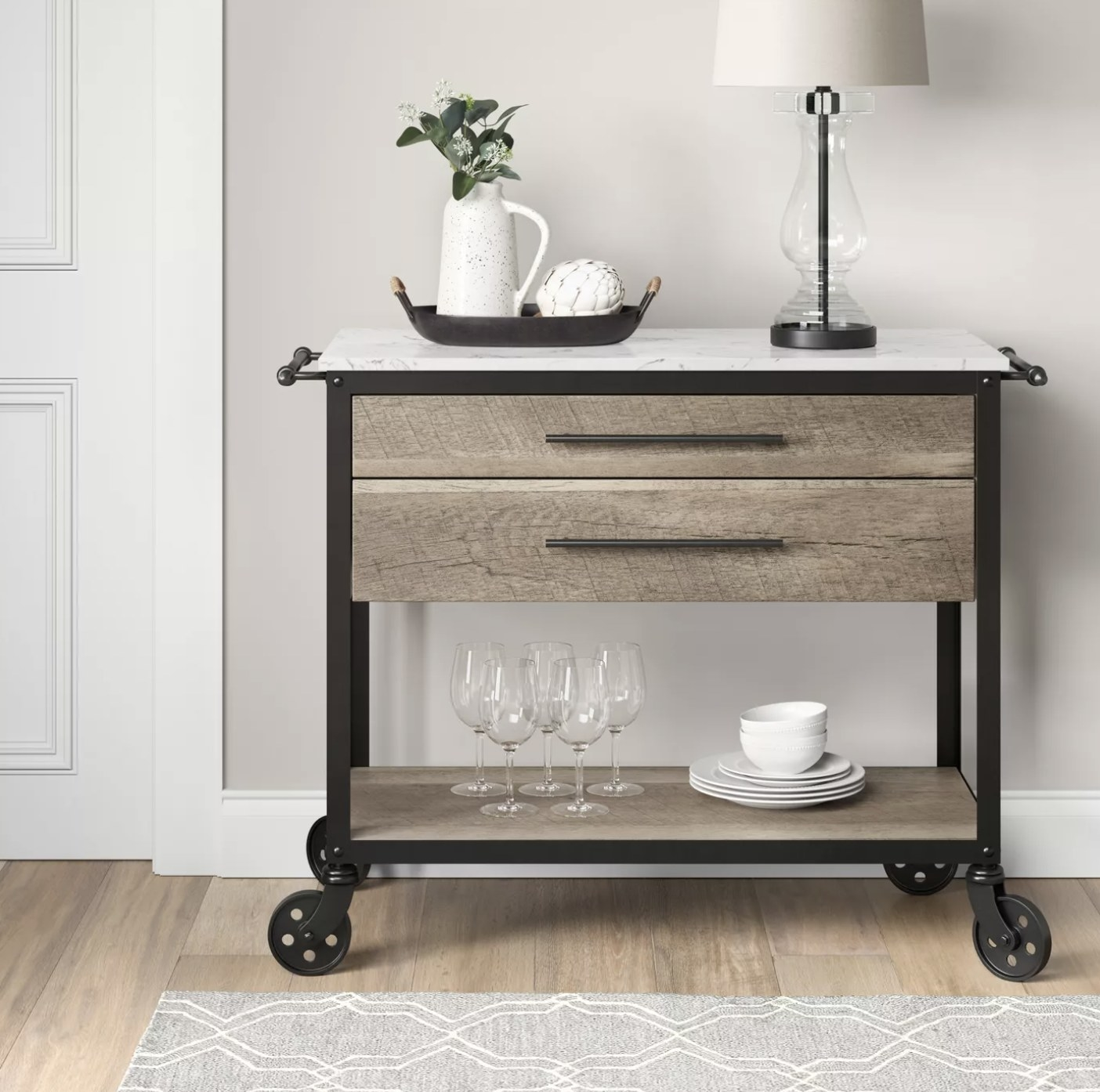 A birchwood colored cart with a black metal frame and caster wheels and a white marble top