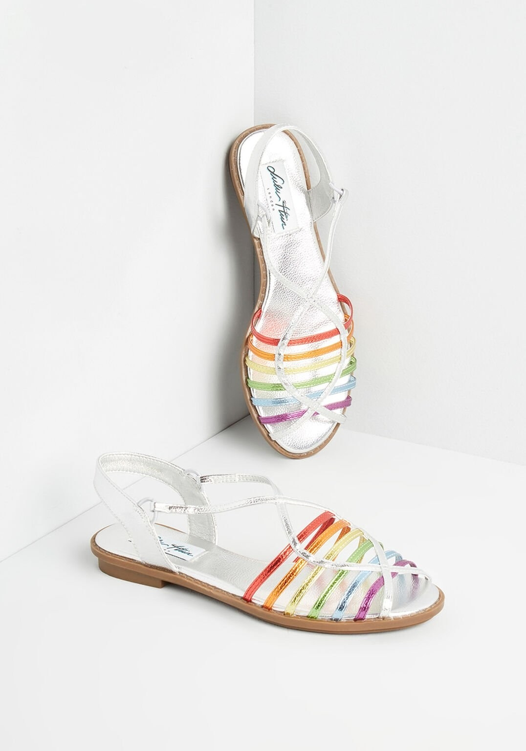 flat sandals with silver and rainbow colored straps