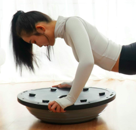 Model uses balance ball trainer to do core exercises