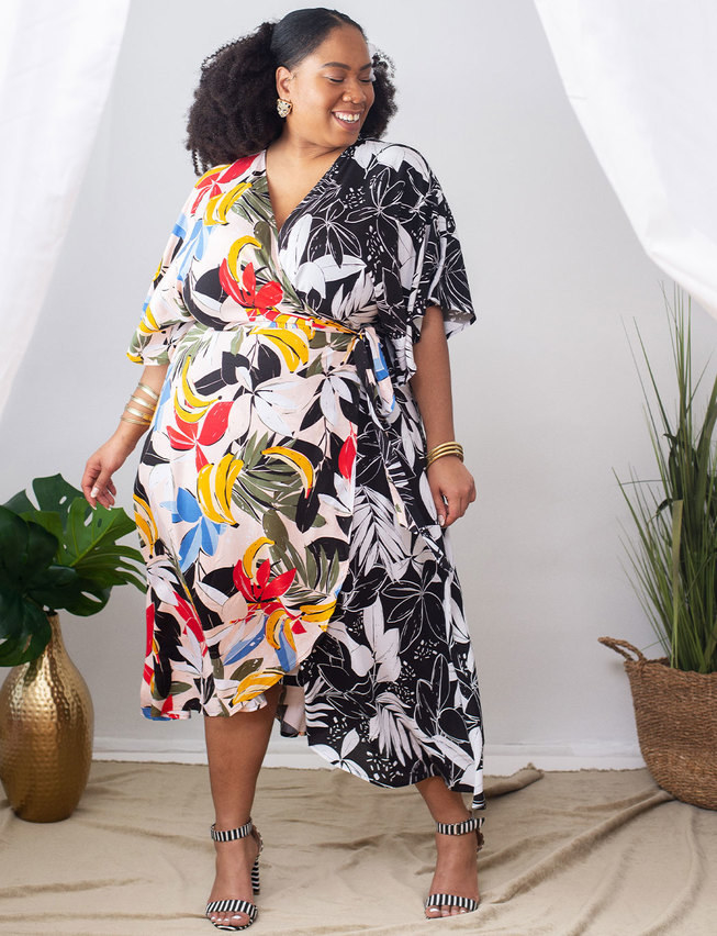 model wears a wrap dress that is half colorful tropical print with bananas and the other half is black and white flowers