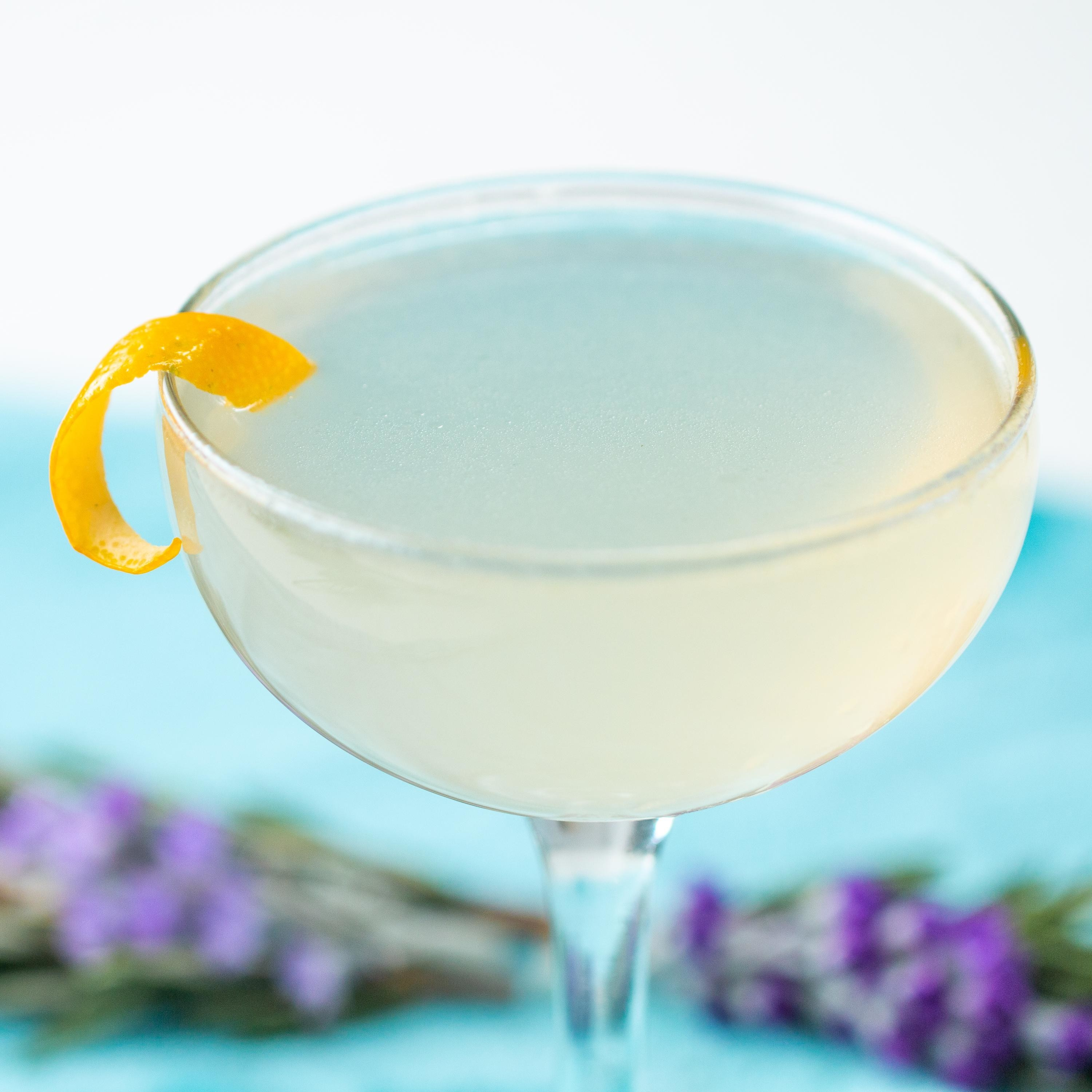 Glass filled with an opaque liquid and garnished with a twist of lemon peel.