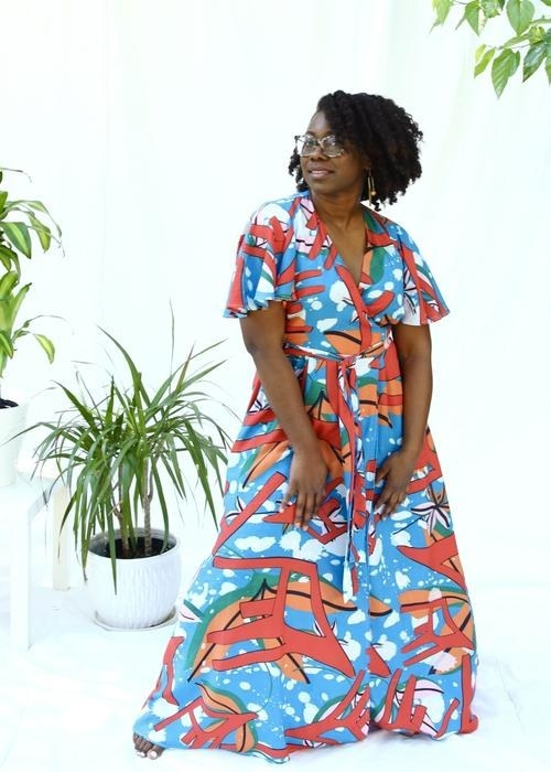 model wears blue maxi dress  with pattern that looks like white drip paint, orange leaves, and red geometric shapes that look like chairs
