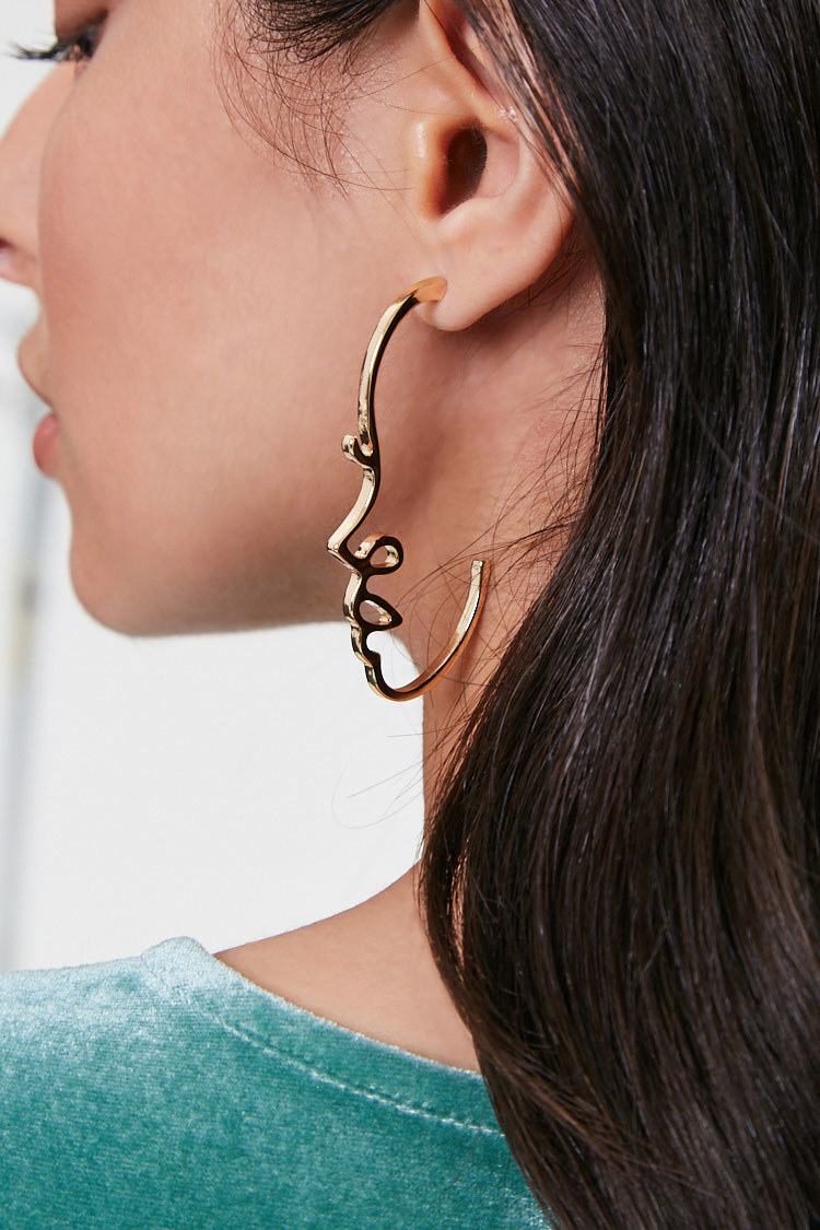The earrings, which look like the profile of a face