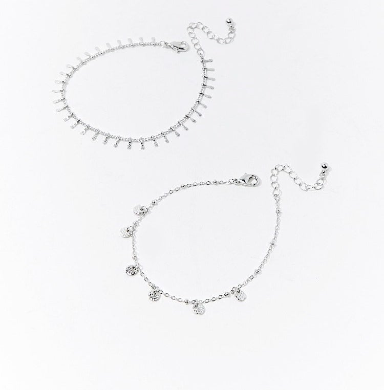 The set, which includes two anklets with different size disc charms