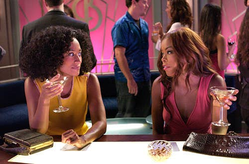 Two women sitting at a bar sipping drinks from martini glasses.