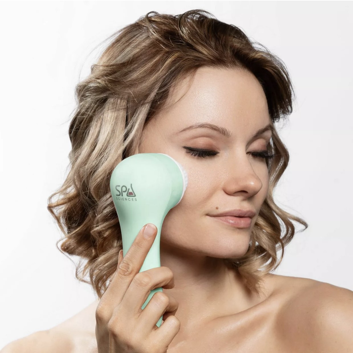 A model using the cleansing brush on their face
