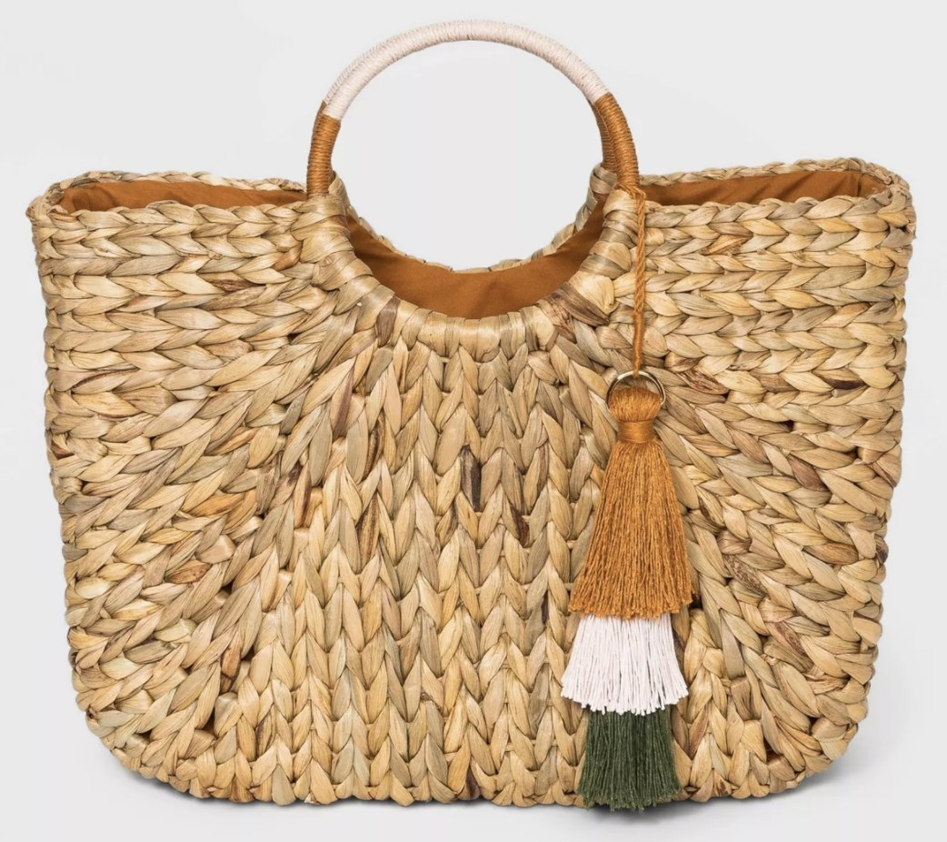 A straw tote with a bangle handle and a tassel hanging from it