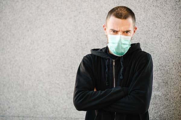A photo of a man angrily wearing a face mask