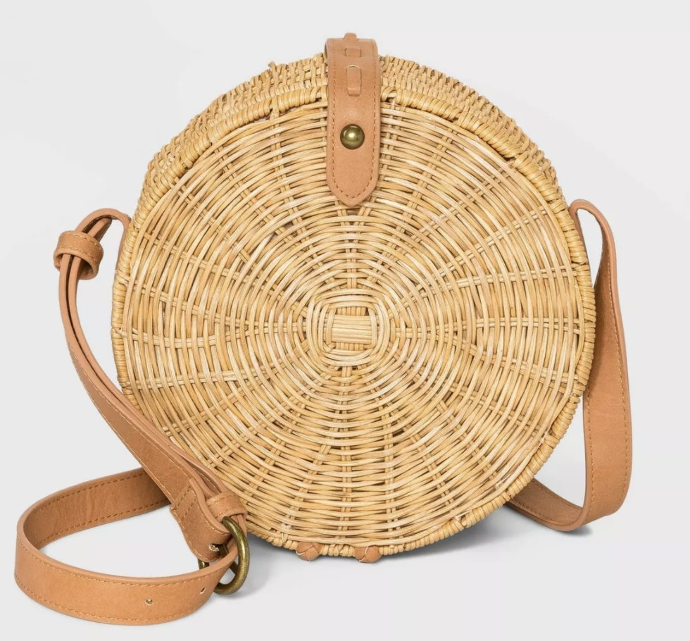 A circle-shaped straw cross body bag with a beige faux-leather strap