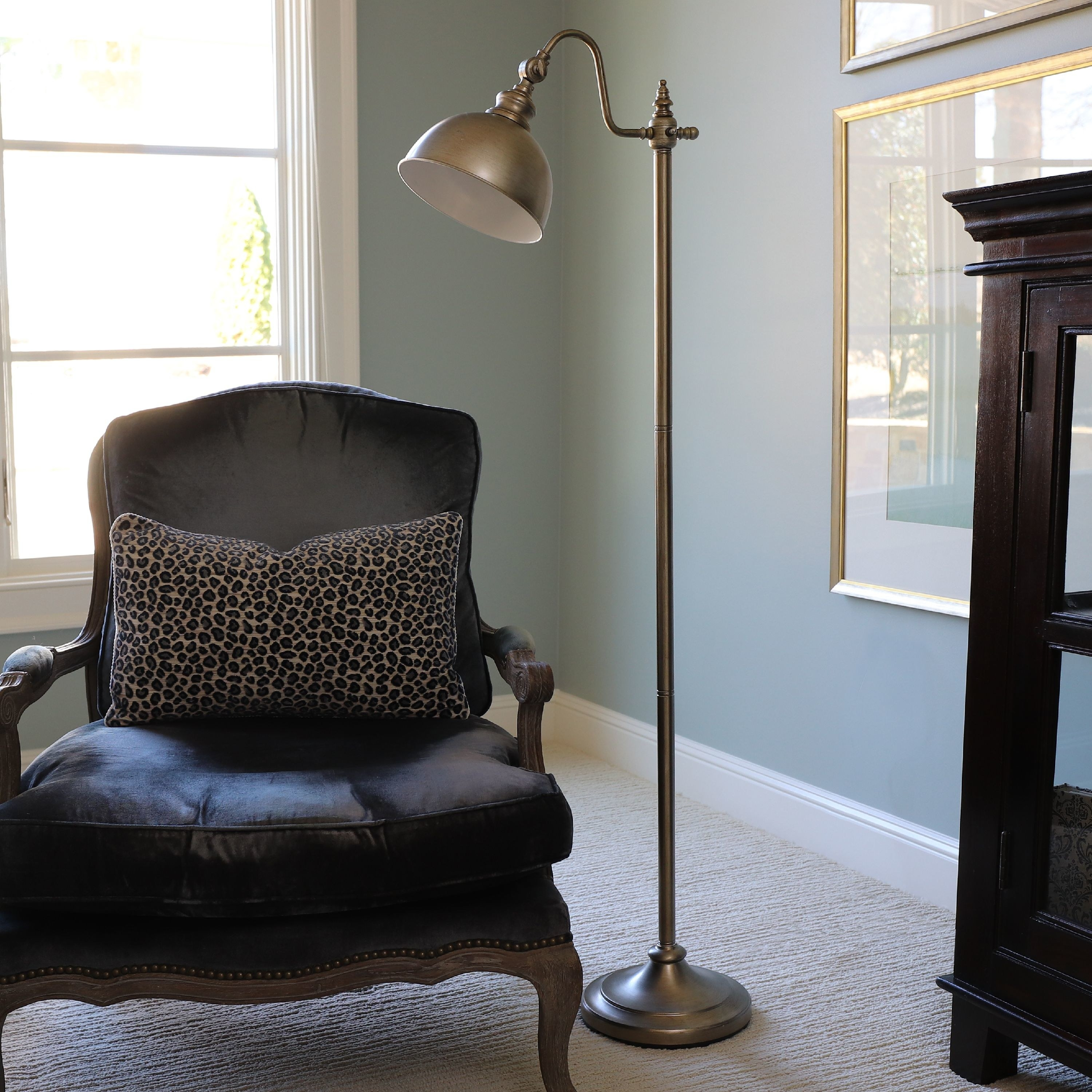 A 56-inch tall brass floor lamp with a round base