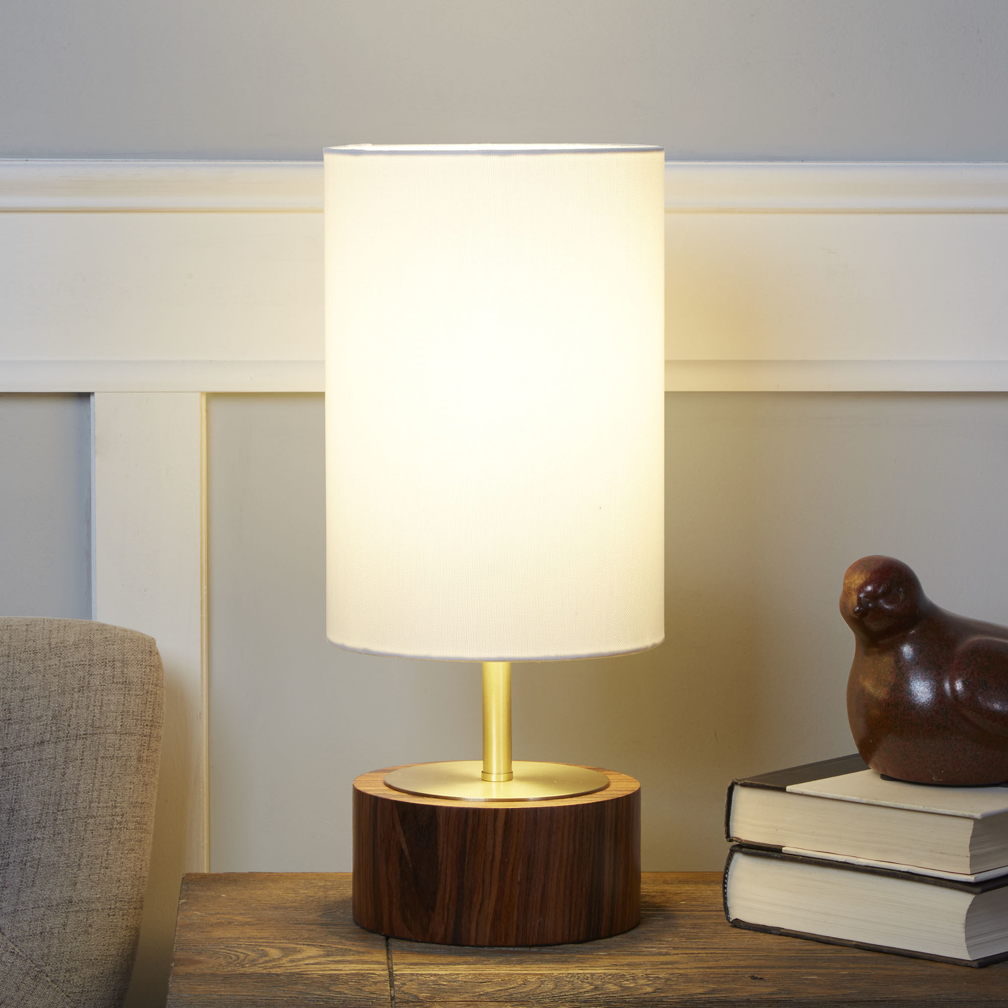 A tall round lamp with a wooden base, gold metal stem, and off-white lampshade