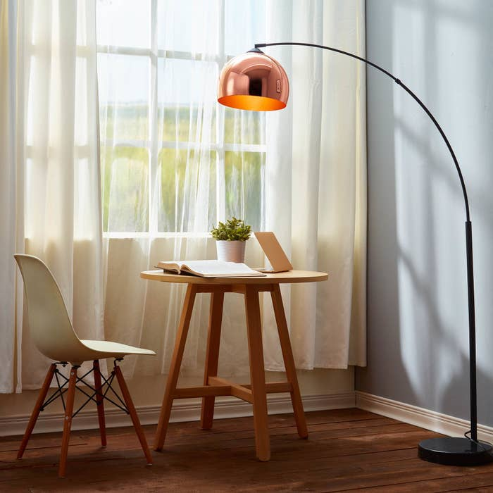 A chrome floor lamp with a curved black stand