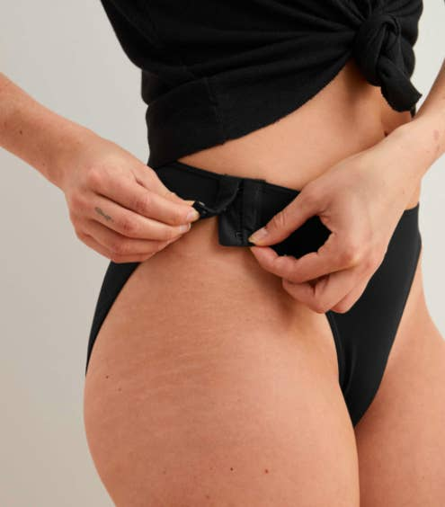 model wearing high waisted black bikini underwear that unhook at that hip for easy removal