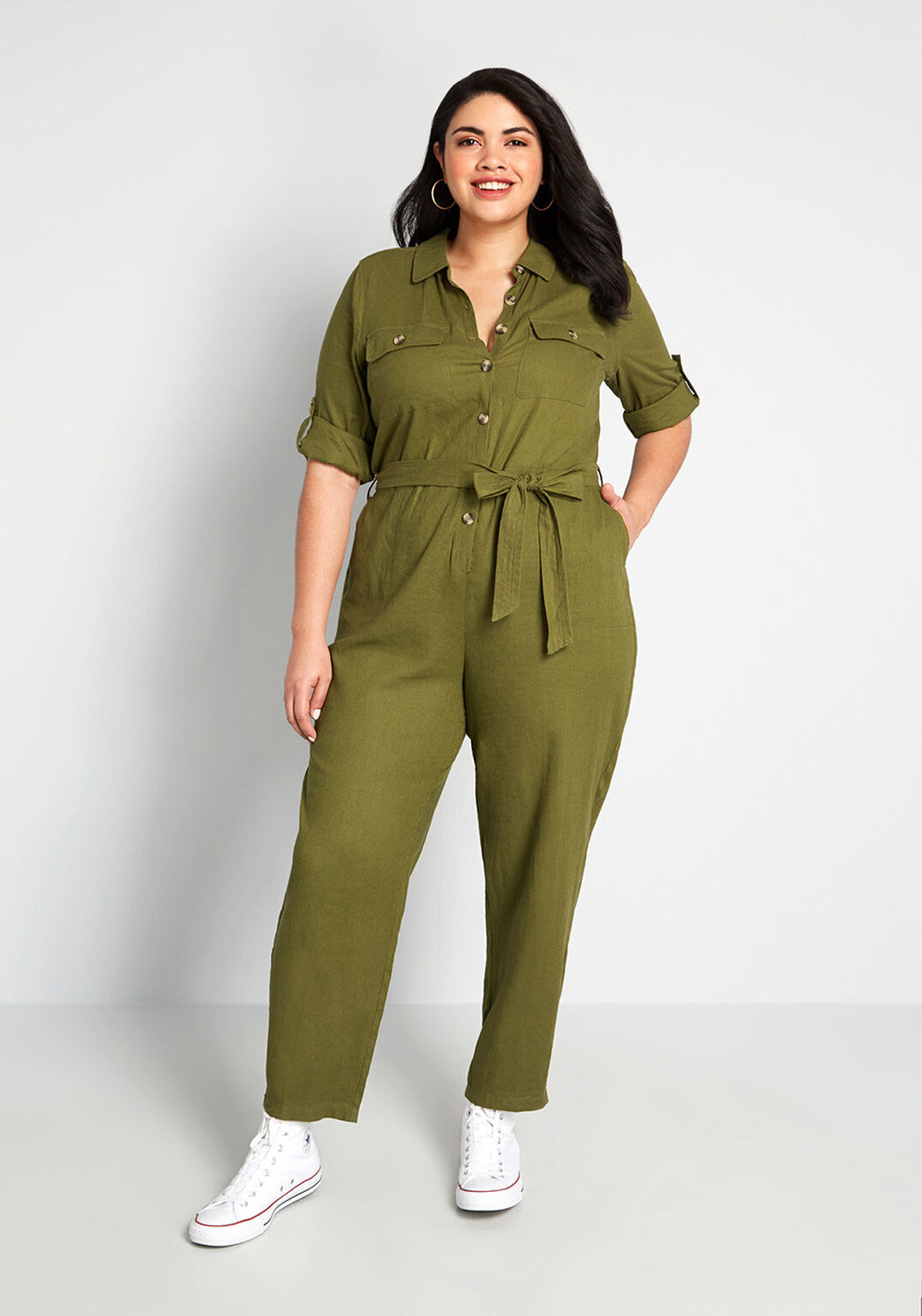 model wearing sleeved olive jumpsuit with tie belt