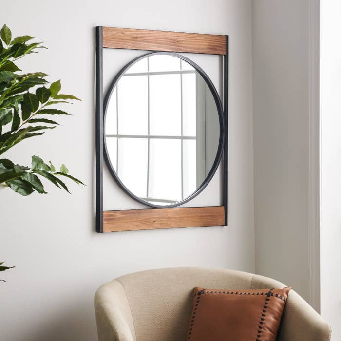 A circle shaped mirror with a square shaped metal black frame