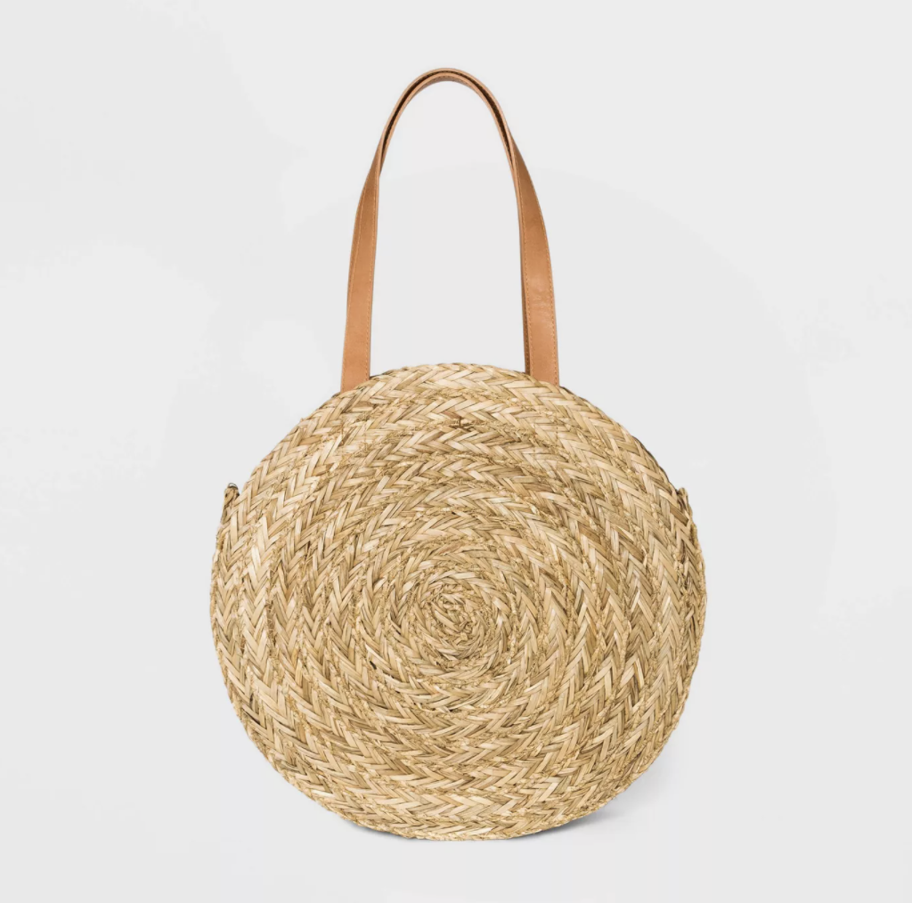 a round straw woven bag with a darker brown leather handle