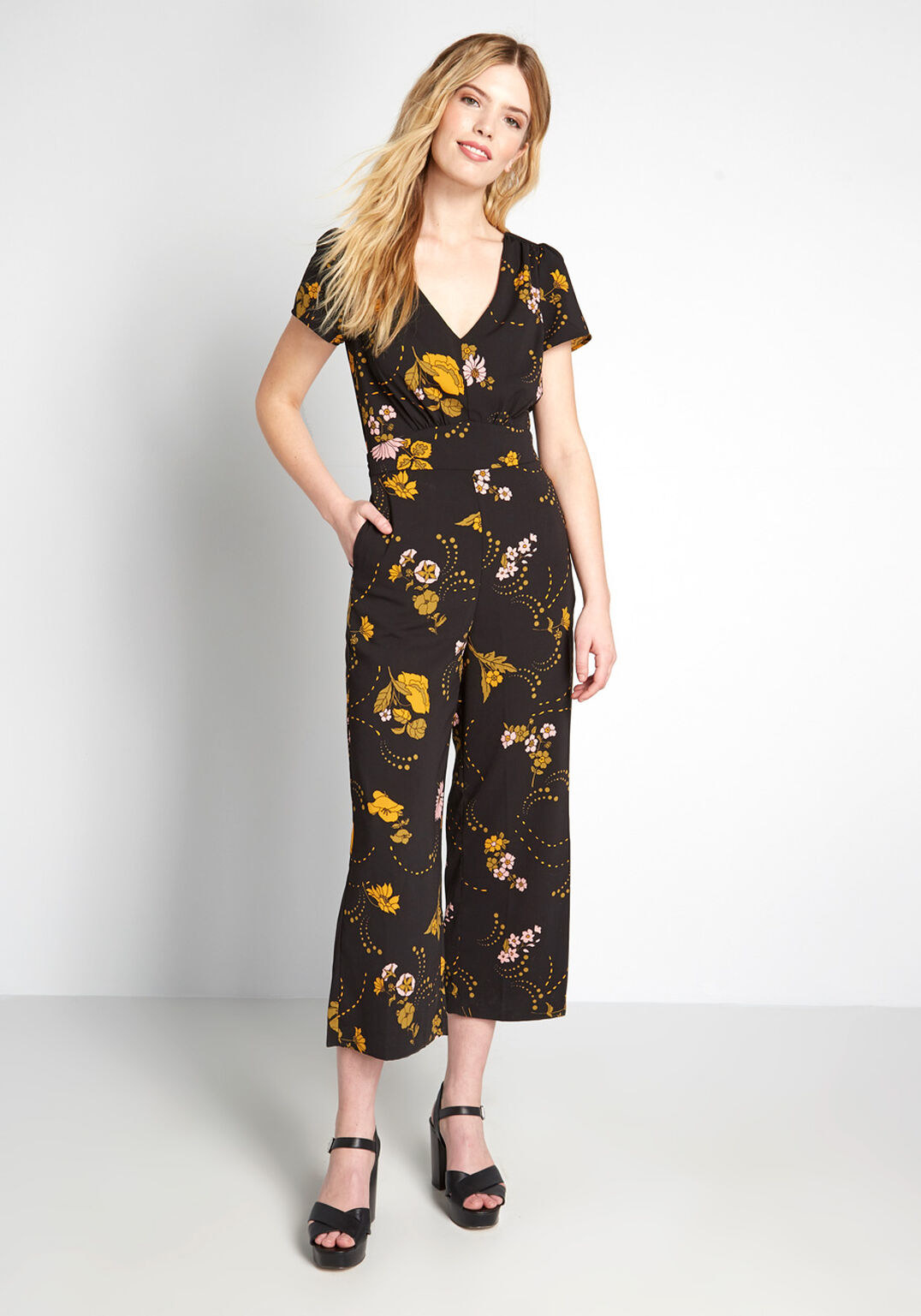model wearing cropped V-neck black and floral jumpsuit