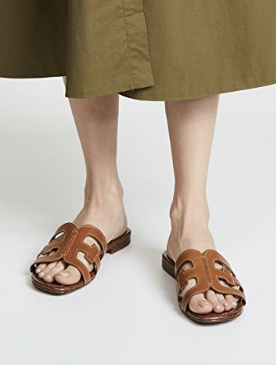 Model  wearing the sandals with cut-out design across the top of the foot in brown