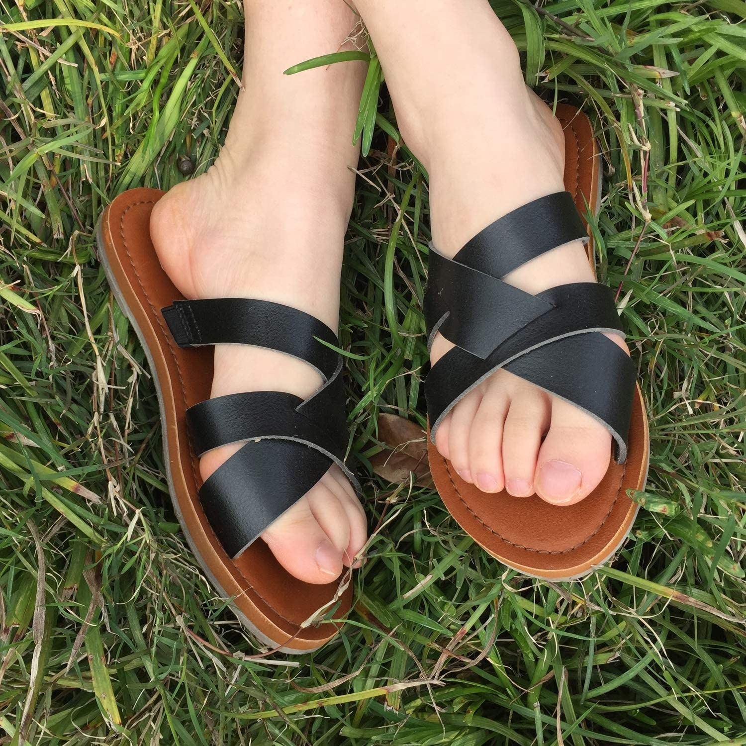 Model wearing the sandals with brown soles and black crossed straps across the top
