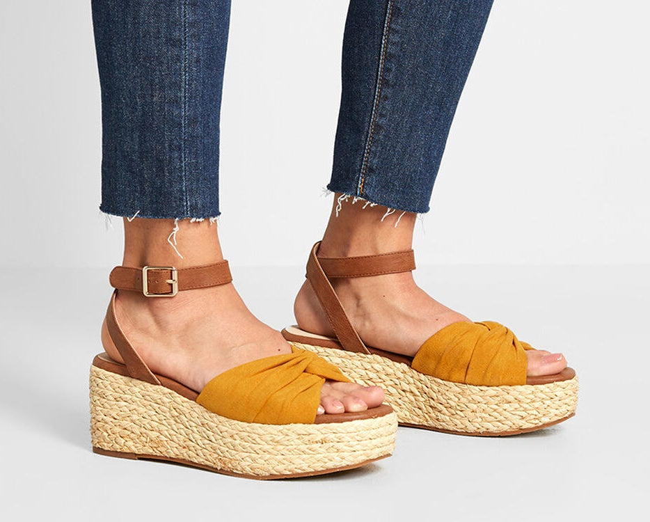 model wearing ankle strap sandals with mustard yellow strap