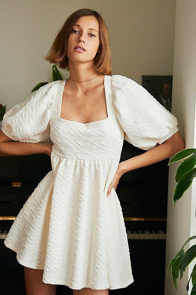 model in white textured dress with short puffy sleeves and square neck