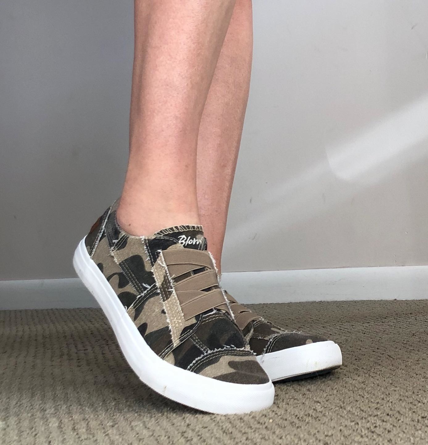 Reviewer wearing cmouflage shoes with white soles